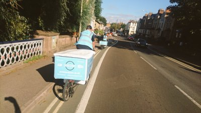 Two couriers cycling down Botley road, Oxford